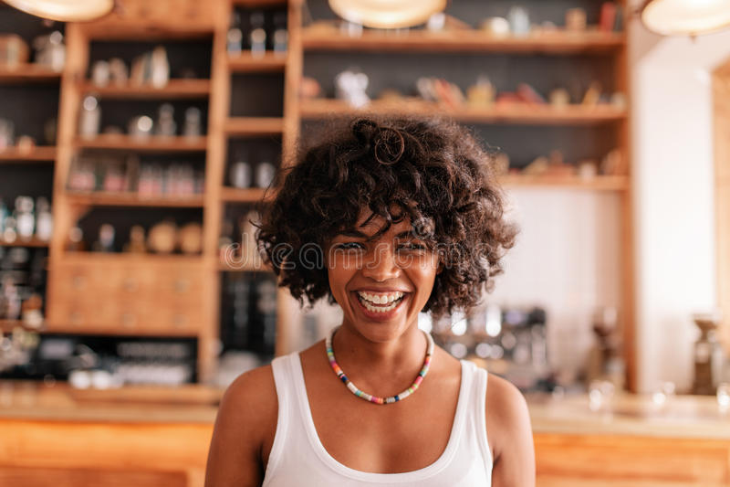 Jovem mulher feliz que ri em um café foto de stock royalty free