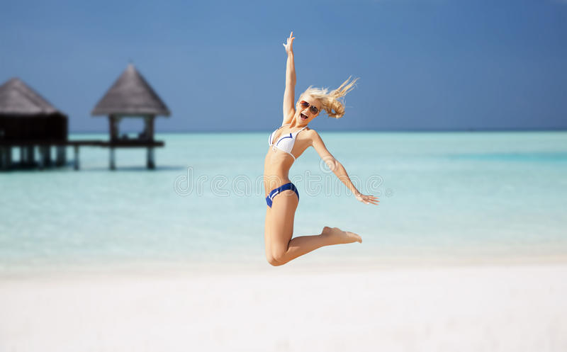 Jovem mulher feliz que salta sobre a praia exótica imagens de stock
