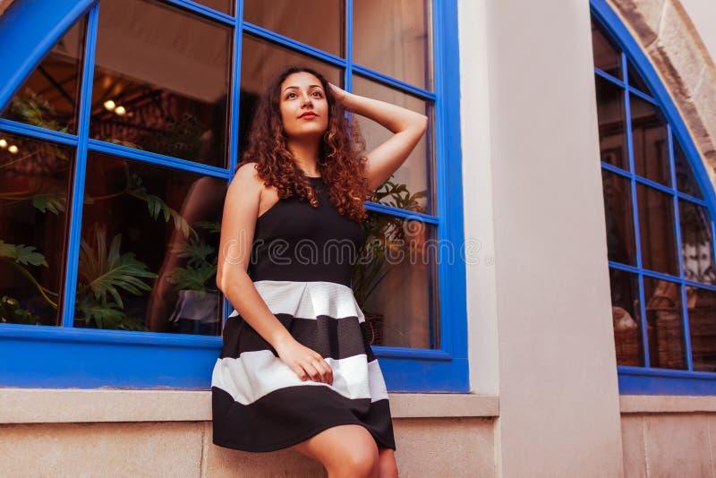 Jovem mulher feliz que senta-se contra a janela azul Retrato exterior do sorriso do Oriente Médio bonito da menina imagem de stock royalty free