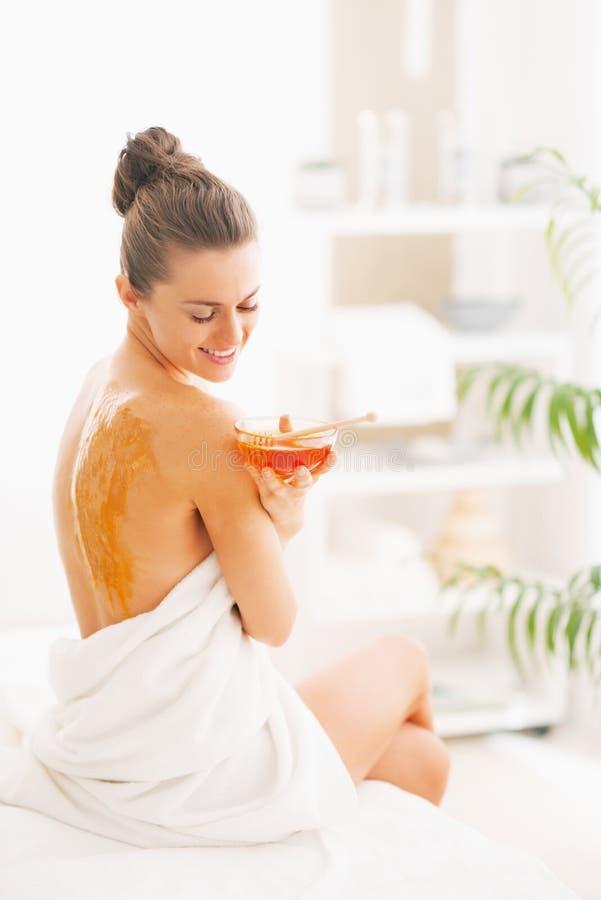 Jovem mulher feliz que senta-se na tabela da massagem com placa do mel fotografia de stock