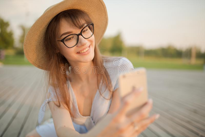 Jovem mulher feliz que senta-se no parque Sorrir faz o selfie fotografia de stock royalty free