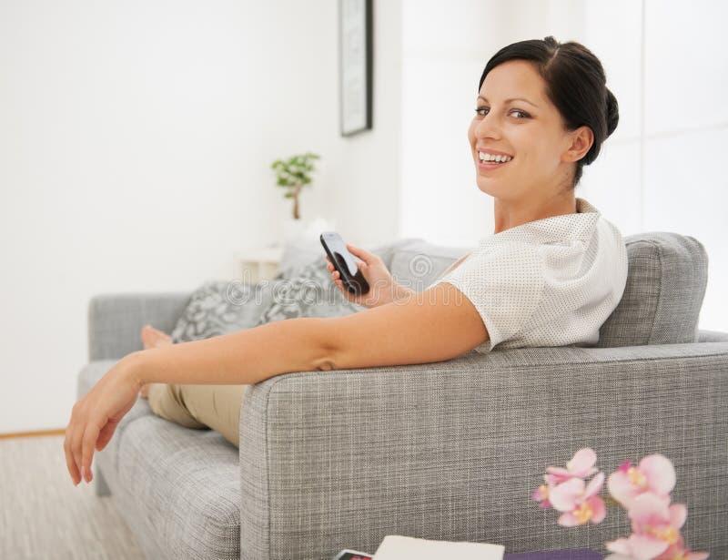 Download Mulher Feliz Que Senta-se No Sofá E Que Guardara O Telefone Imagem de Stock - Imagem de home, apartamento: 29827599
