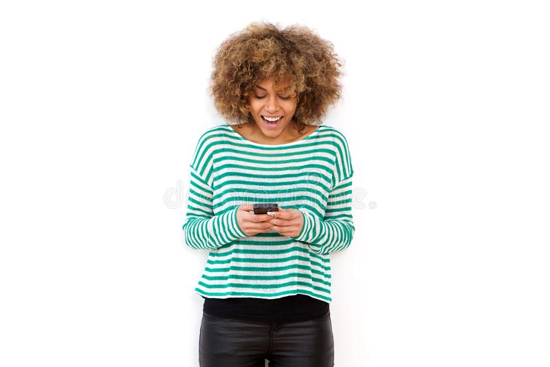 Jovem mulher feliz que sorri e que olha o telefone celular imagens de stock royalty free
