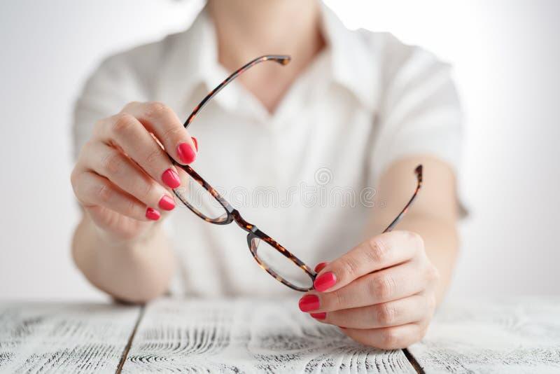 Jovem mulher feliz que tenta seus vidros novos, conceito do cuidado do olho fotos de stock royalty free