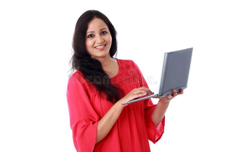 Jovem mulher feliz que trabalha com um laptop foto de stock