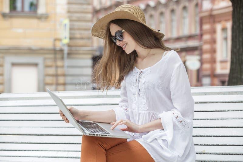 Jovem mulher feliz que trabalha com um portátil que senta-se em um banco fotografia de stock