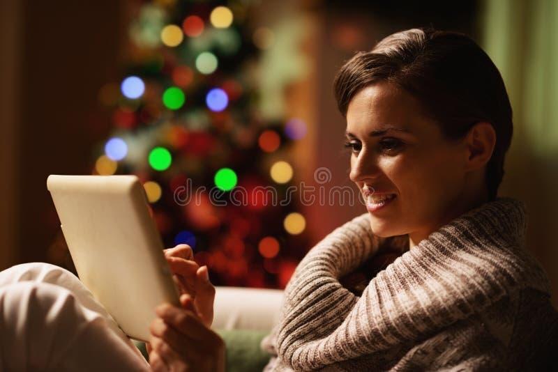 Jovem mulher feliz que usa o PC da tabuleta na frente da árvore de Natal foto de stock royalty free