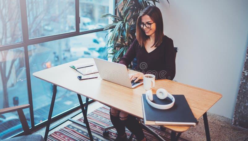 Jovem mulher feliz que usa o portátil móvel para fazer a conversação do negócio com os sócios durante o processo do trabalho no e fotografia de stock royalty free