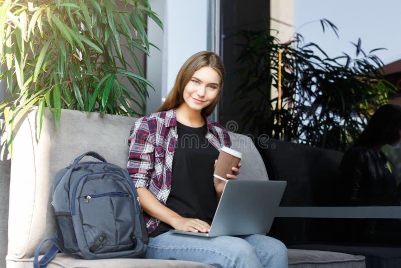 Jovem mulher feliz que usa o portátil no café foto de stock royalty free