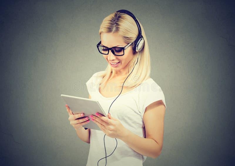 Jovem mulher feliz que usa o tablet pc que escuta a música com fones de ouvido imagem de stock royalty free