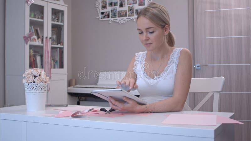 Jovem mulher feliz que usa sua tabuleta ao sentar-se na tabela do ofício foto de stock royalty free