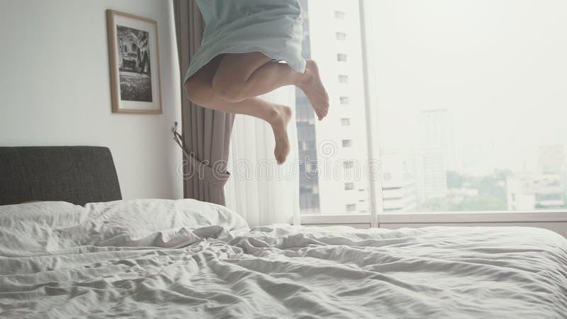 A jovem mulher feliz salta na cama em casa que tem o divertimento na cama em um apartamento luxuoso Feche acima dos pés fotografia de stock royalty free