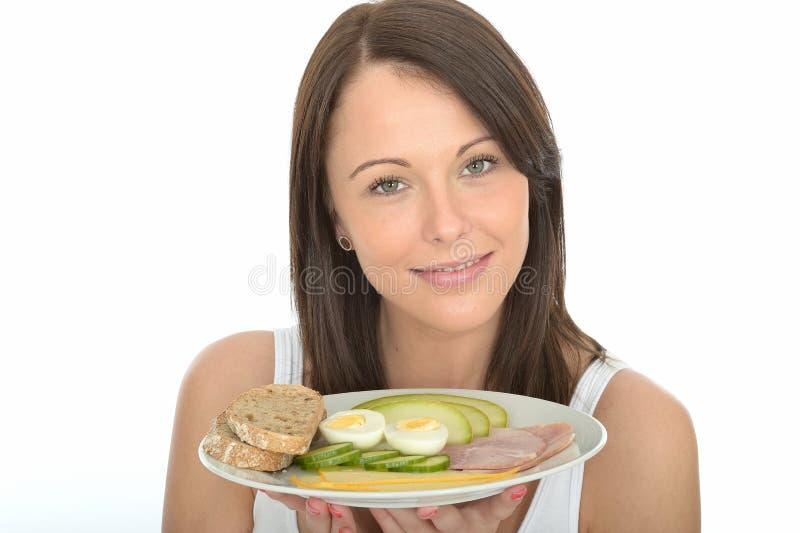 Jovem mulher feliz saudável que guarda uma placa do café da manhã norueguês do estilo imagem de stock