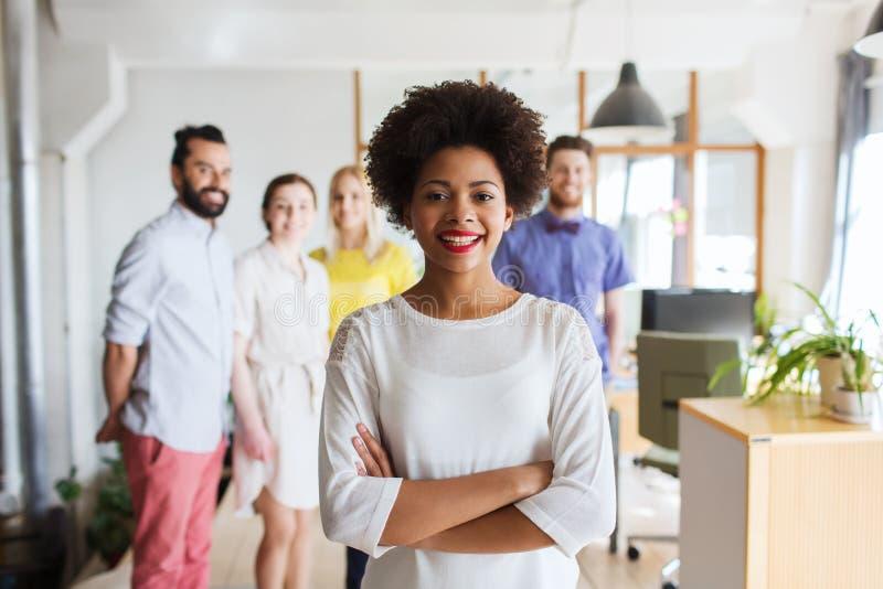 Jovem mulher feliz sobre a equipe criativa no escritório imagem de stock