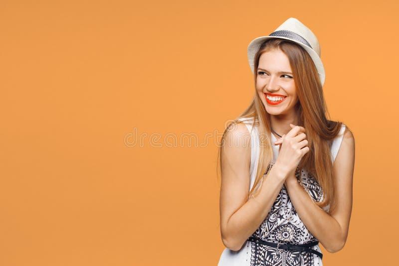 Jovem mulher feliz surpreendida que olha lateralmente no excitamento Isolado sobre o fundo alaranjado fotografia de stock