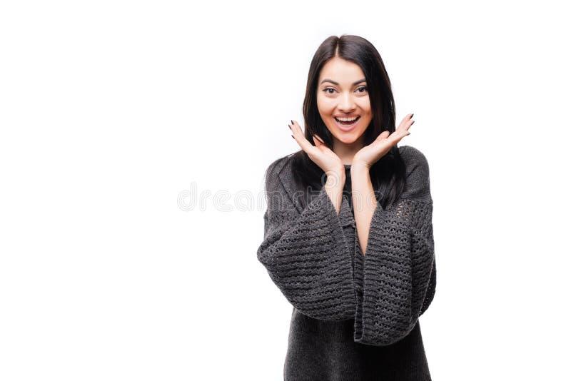Jovem mulher feliz surpreendida que olha lateralmente no excitamento sobre o fundo branco fotografia de stock