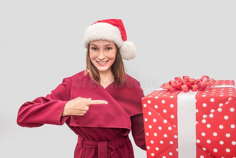 A jovem mulher feliz veste o revestimento e o chapéu vermelhos do Natal Olha na câmera e sorri Pontos modelo na caixa vermelha gr imagens de stock