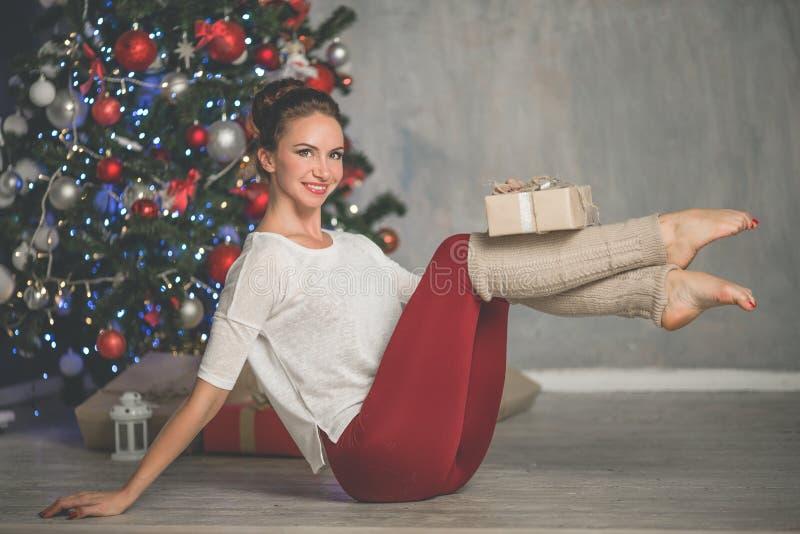 A jovem mulher flexível bonita está fazendo esticando a árvore em casa próximo decorada do xmas da forma do exercício, os esporte imagem de stock royalty free