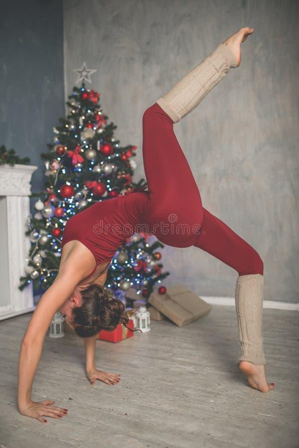 A jovem mulher flexível bonita está fazendo esticando a árvore em casa próximo decorada do xmas da forma do exercício, os esporte imagens de stock