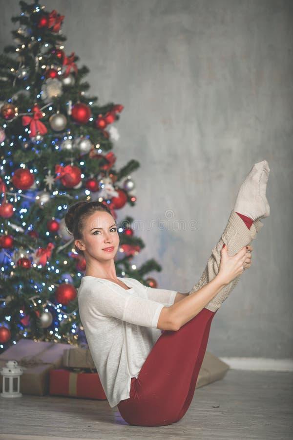 A jovem mulher flexível bonita está fazendo esticando a árvore próximo decorada do xmas da forma do exercício, os esportes e o co fotos de stock royalty free