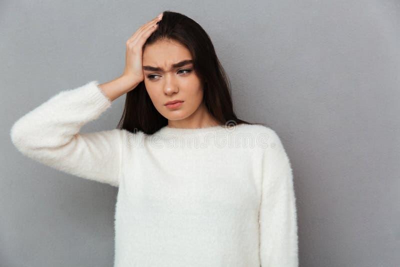 Jovem mulher forçada na camiseta branca que tem a dor de cabeça, olhando a foto de stock