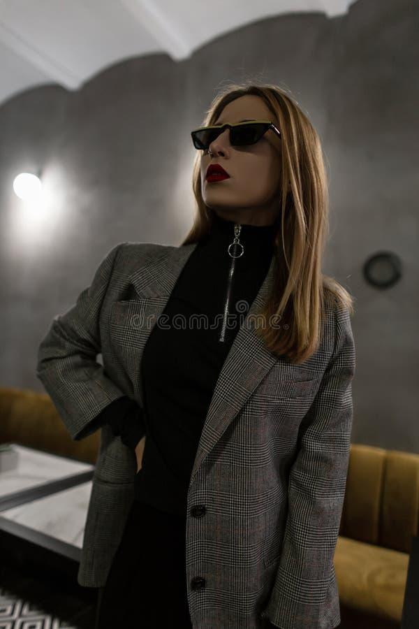 Jovem mulher fresca bonita do moderno em óculos de sol na moda pretos no revestimento quadriculado do vintage cinzento com os bor imagem de stock