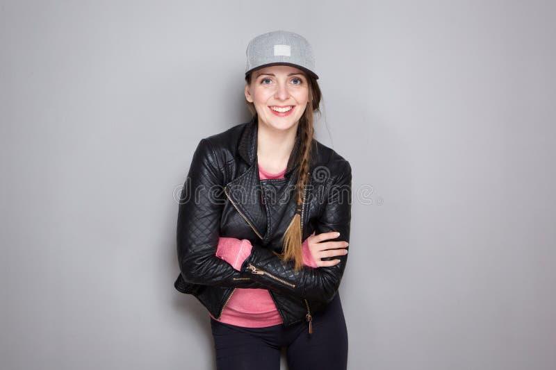 Jovem mulher fresca com posição do casaco de cabedal e do chapéu pela parede cinzenta imagens de stock royalty free