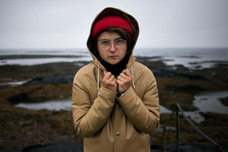 Jovem mulher fria e shievering na capa de chuva fotografia de stock