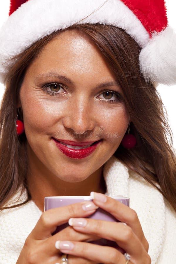 Jovem mulher fria em um chá sorvendo do café do chapéu de Santa foto de stock royalty free
