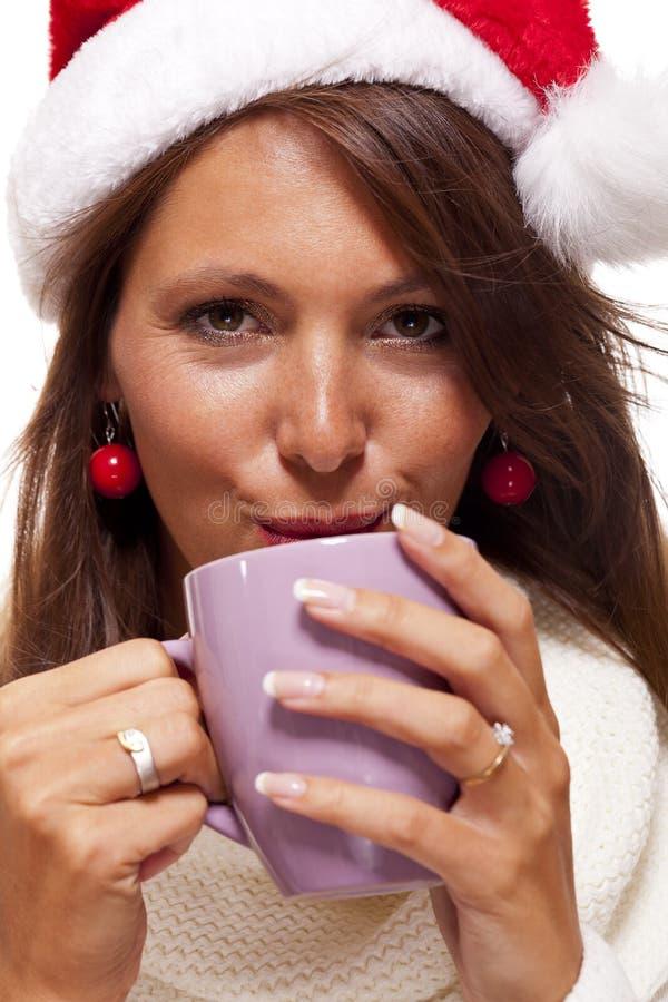 Jovem mulher fria em um chá sorvendo do café do chapéu de Santa fotos de stock royalty free