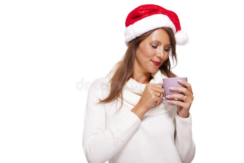 Jovem mulher fria em um chá sorvendo do café do chapéu de Santa foto de stock