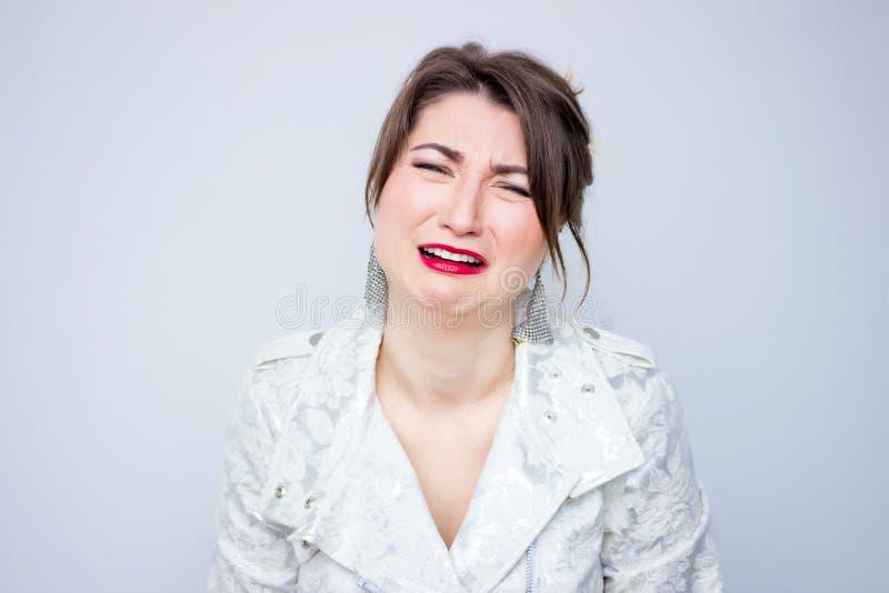 A jovem mulher frustrante que grita no revestimento elegante branco, sere o batom do vermelho da composição foto de stock