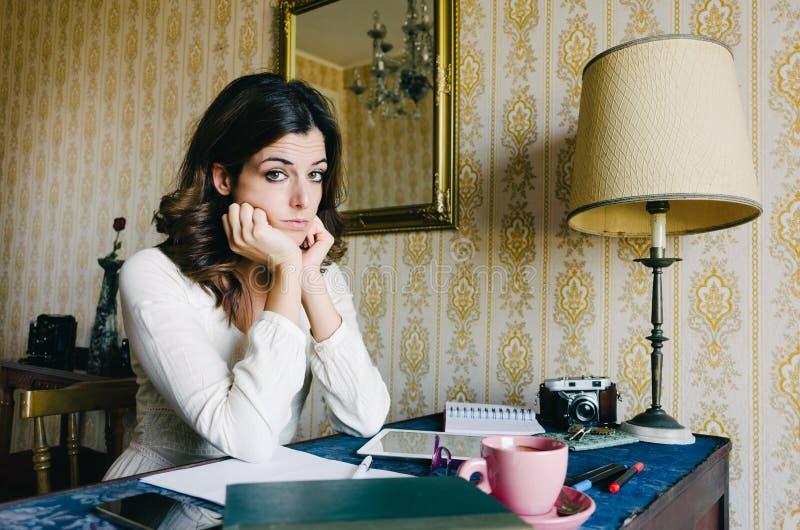 Jovem mulher furada e cansado que trabalha em casa imagens de stock royalty free