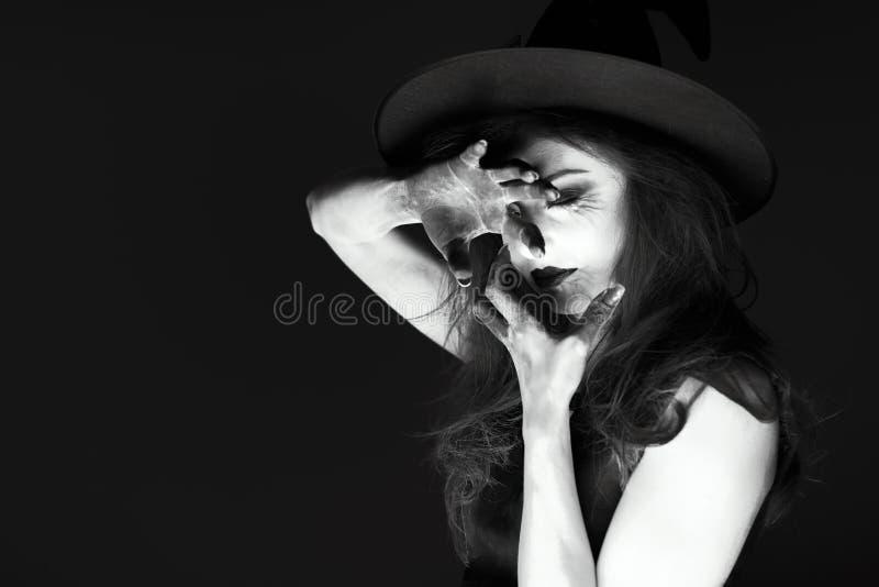 A jovem mulher gótico escura no traje do Dia das Bruxas da bruxa com composição e cede o fundo preto com a vela, isolada fotografia de stock royalty free