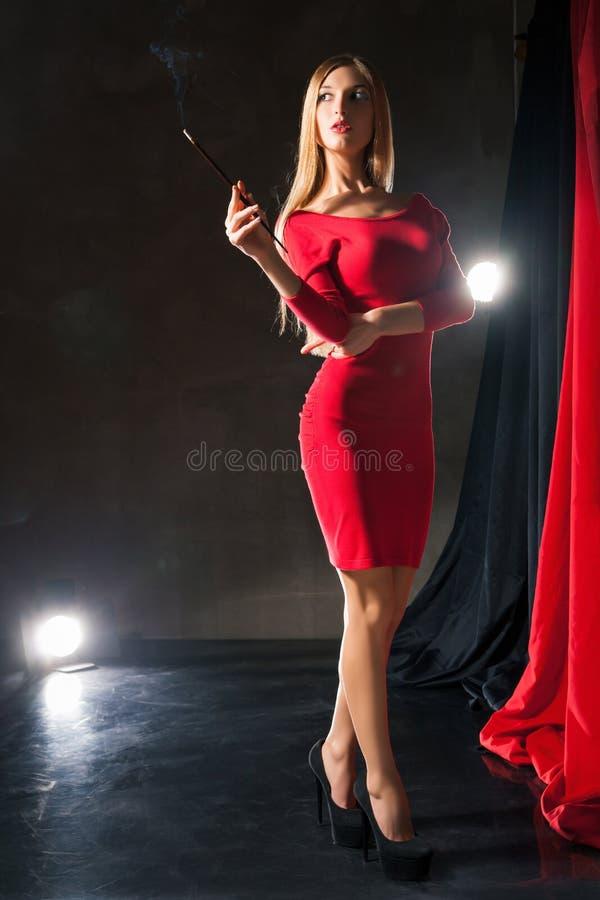 Jovem mulher glamoroso com o cigarro que está sobre fotografia de stock royalty free