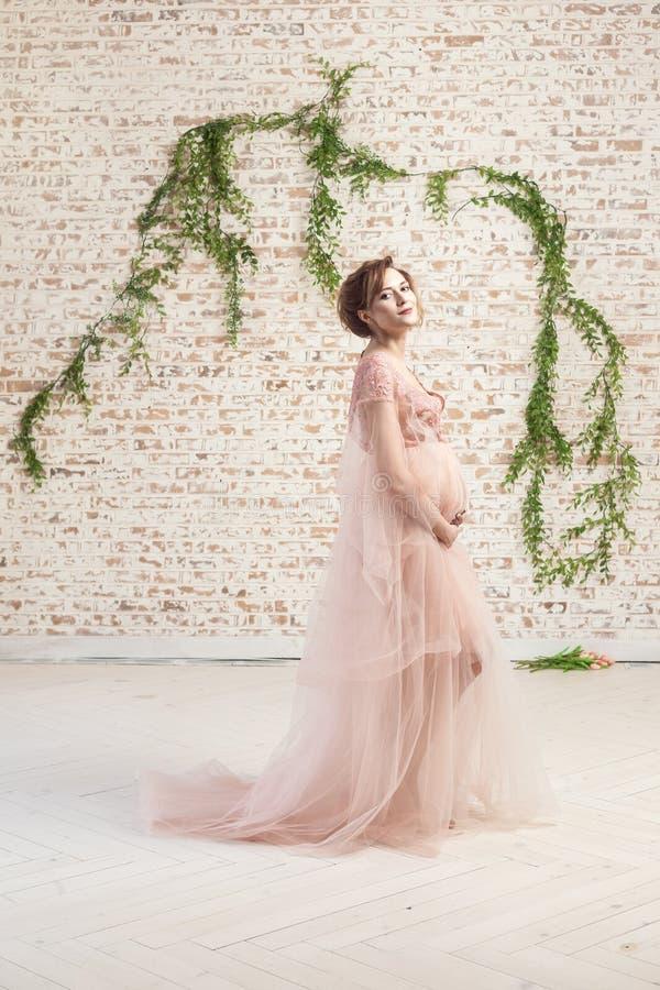 Jovem mulher grávida bonita alegre sensual na posição cor-de-rosa do vestido e guardar com amor sua barriga imagens de stock royalty free