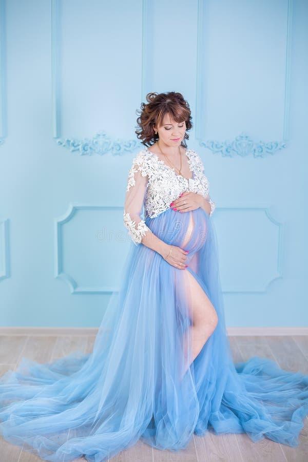Jovem mulher grávida bonita que veste o vestido azul luxuoso da roupa interior, retrato do estúdio da senhora de surpresa com cab imagem de stock