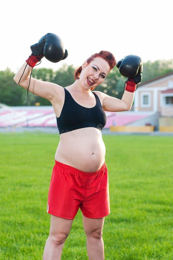 Jovem mulher grávida com luvas de encaixotamento fotos de stock