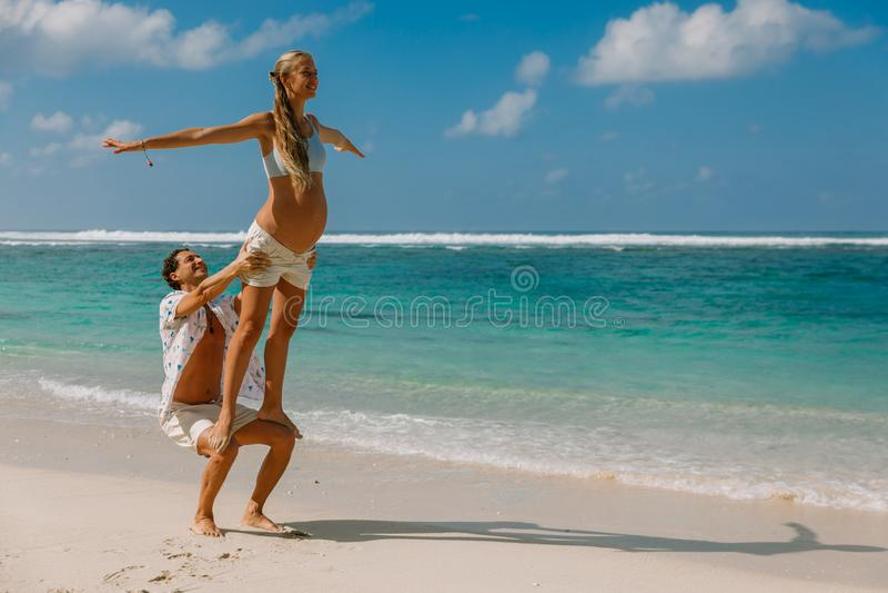 Jovem mulher grávida com o marido que espera o bebê com pose da ioga imagens de stock