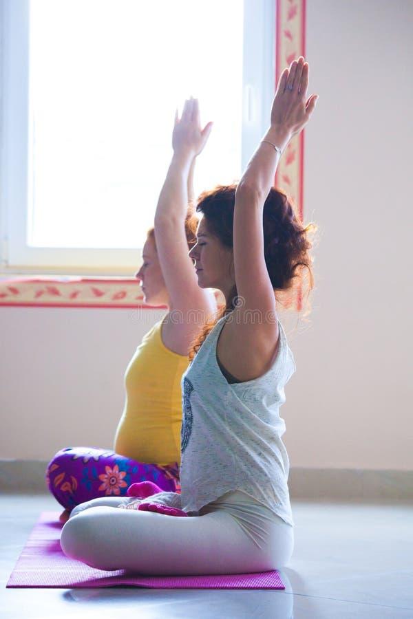 Jovem mulher grávida na classe da ioga interna com instrutor foto de stock royalty free
