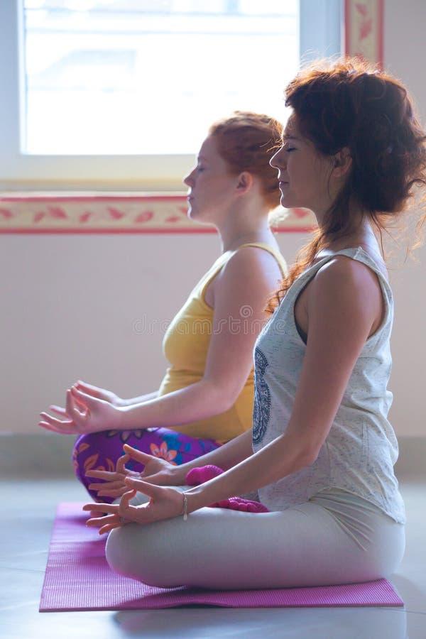 Jovem mulher grávida na classe da ioga interna com instrutor fotografia de stock royalty free