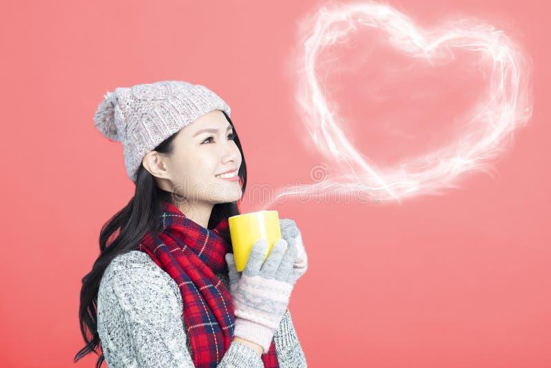 a jovem mulher guarda um copo com café ou chá quente fotografia de stock