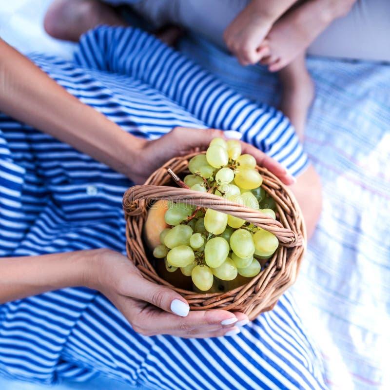 A jovem mulher guarda uma cesta com uvas imagem de stock