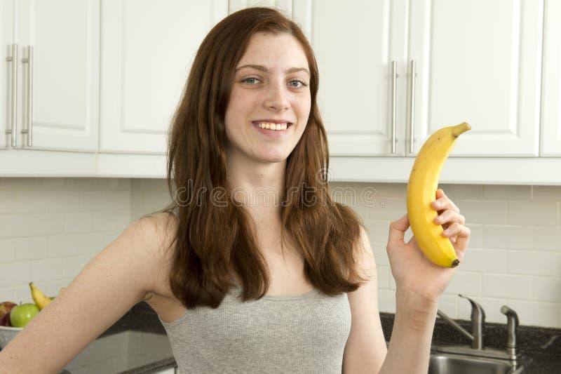 A jovem mulher guardara a banana fotos de stock