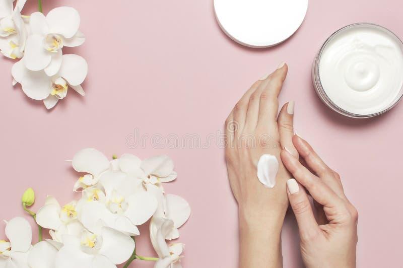 A jovem mulher hidrata sua mão com loção de creme cosmética abriu o recipiente com Phalaenopsis branco do leite do corpo do creme imagem de stock