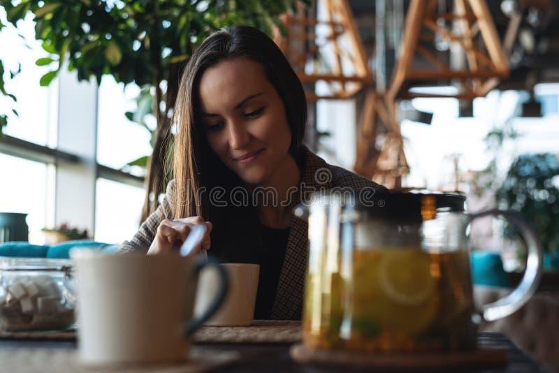A jovem mulher impede a tisana com o espinheiro cerval de mar no copo, no bule e na caneca de vidro do primeiro plano foto de stock royalty free