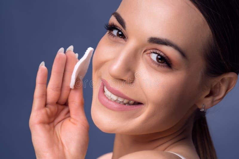 A jovem mulher importa-se com o abrandamento da pele da cara, lazer, pescoço, innoc fotos de stock