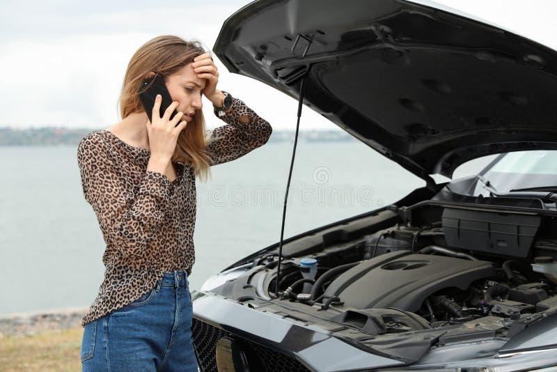 Jovem mulher incomodada que fala no telefone perto de carro quebrado fotos de stock royalty free