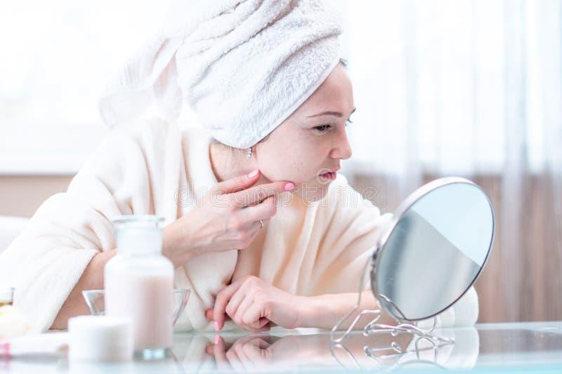 A jovem mulher infeliz bonita com uma toalha em sua cabeça detecta a acne em sua cara Higiene e cuidado para a pele foto de stock royalty free