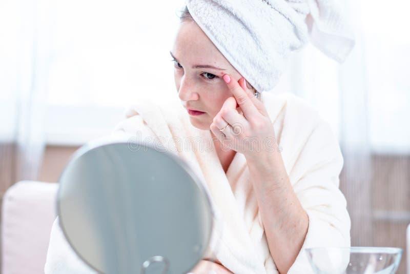 A jovem mulher infeliz bonita detecta a acne em sua cara Conceito da higiene e do cuidado para a pele imagem de stock royalty free